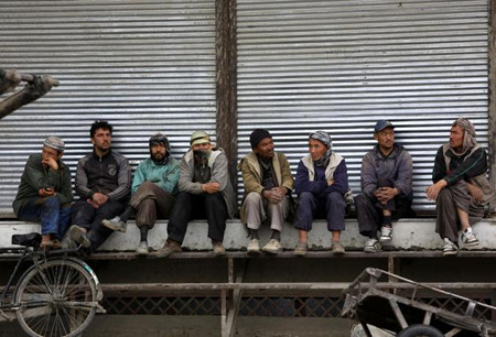afghan workers wait for work