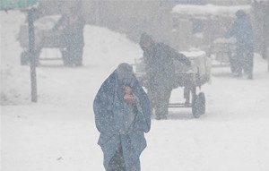 woman walks in cold snow winter afghanistan 300x191